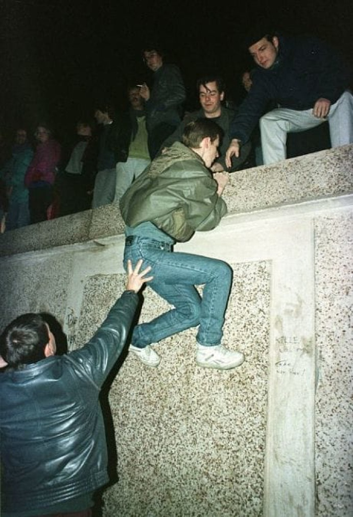 East German citizens climb the Berlin Wall
